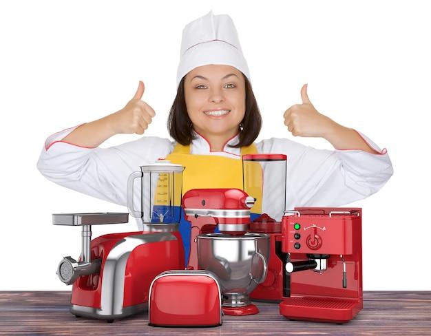 주방 가전 세트입니다. 아름다운 젊은 여성 요리사는 흰색 배경에 있는 빨간색 블렌더, 토스터, 커피 머신, 고기 분쇄기, 식품 믹서, 커피 분쇄기 근처에 엄지손가락을 보여줍니다. 3d 렌더링