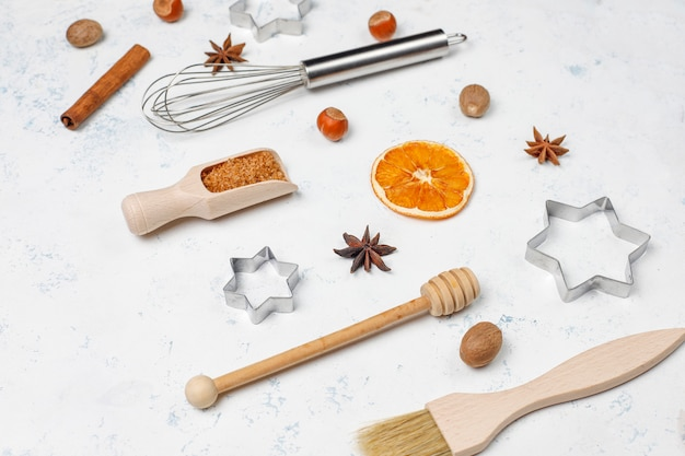 Kitchen baking utensils with spices for cookies and cookie cutters on light surface