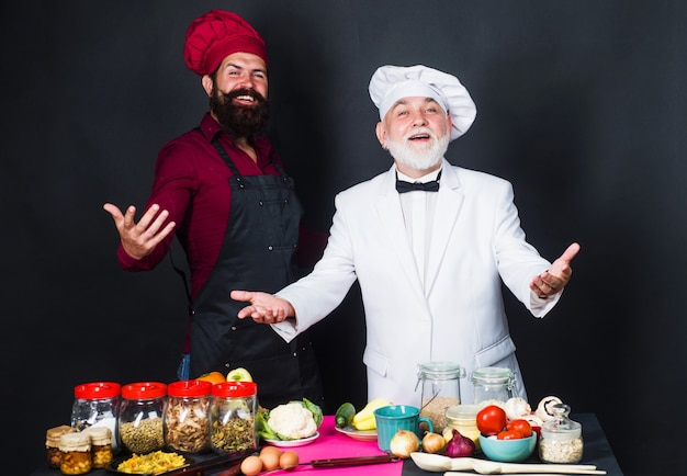 Kitchen battle. two bearded professional chefs in uniform. cooking time.
