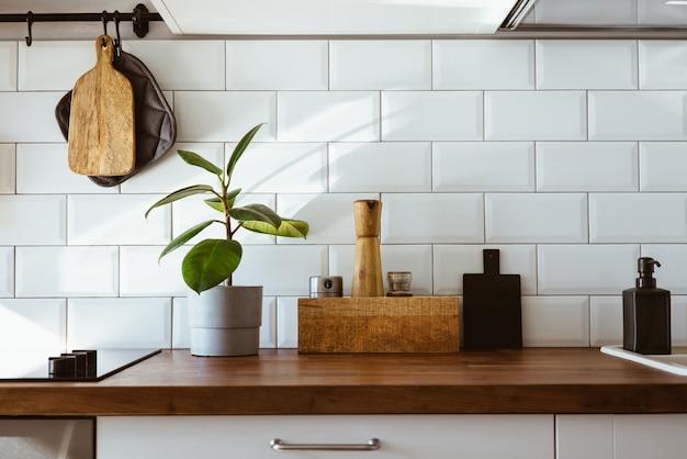 キッチンの真ちゅう製の道具、シェフのアクセサリー。白いタイルの壁と木製の卓上でキッチンをぶら下げます。キッチンの背景に緑の植物早朝の明るい側面図