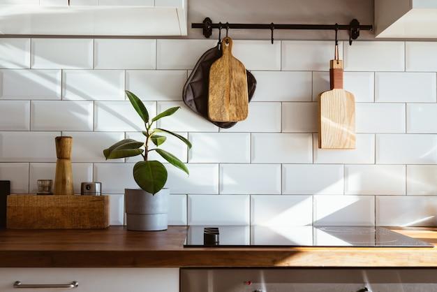 Кухонная посуда из латуни, поварские принадлежности. подвесная кухня с белой плиткой на стене и деревянной столешнице. зеленое растение на кухонном фоне, вид сбоку рано утром