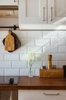Кухонная посуда из латуни, поварские принадлежности. подвесная кухня с белой плиткой на стене и деревянной столешнице. белые цветы на кухонном фоне, вид со стороны света раннего утра