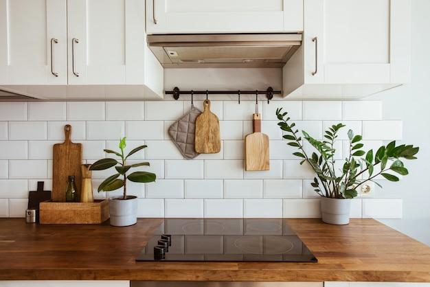 Кухонная посуда из латуни, аксессуары для шеф-повара, подвесная кухня с белой плиткой на стене и деревянной столешницейзеленый ...