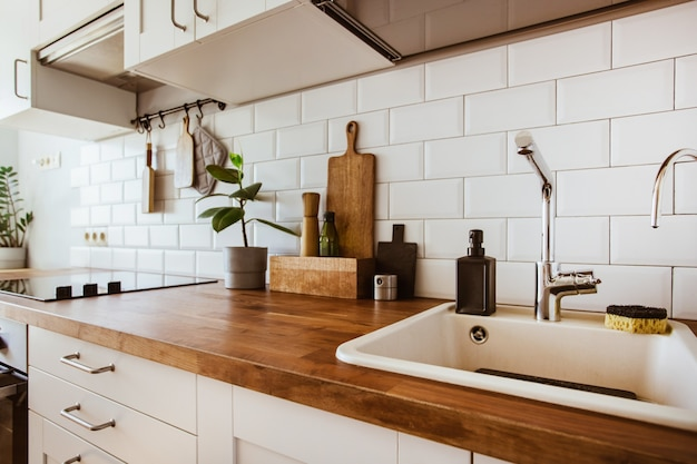 Kitchen brass utensils chef accessories hanging kitchen with white tiles wall and wood tabletopgreen...