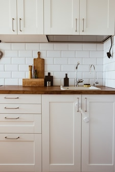 Kitchen brass utensils chef accessories hanging kitchen with white tiles wall and wood tabletopkitch...