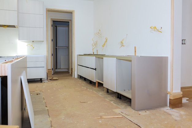 Kitchen cabinets in various stages of installation base for island in center