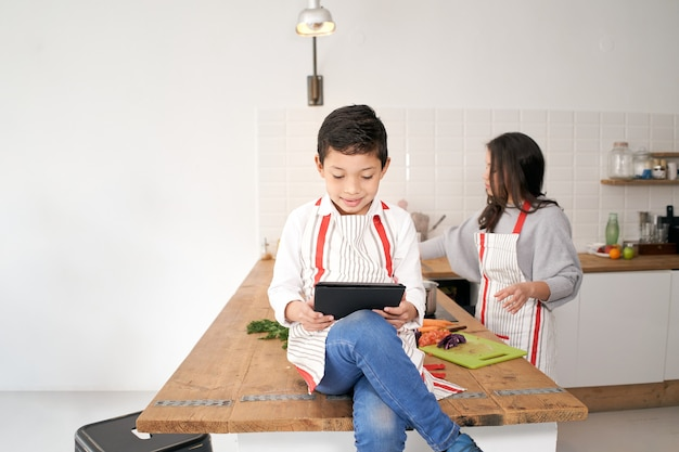 In the kitchen child playing video games with a tablet while his mother cuts vegetables for the meal...