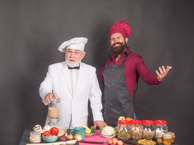 Kitchen cooking two chefs on kitchen beared chef man delicious food male chef in uniform satisfied