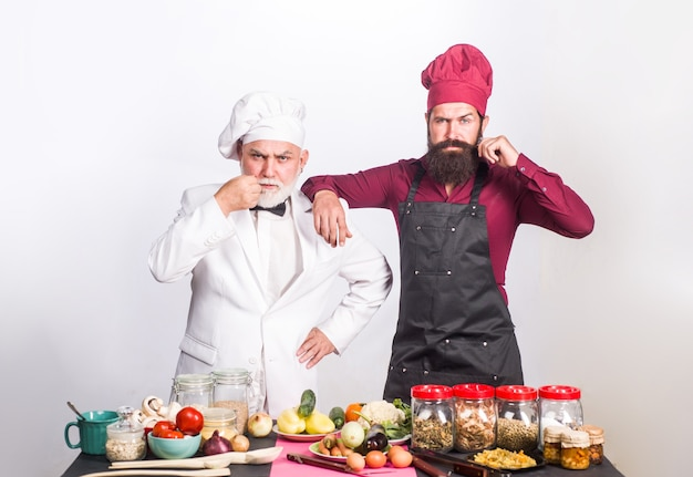 Kitchen cooking two chefs on kitchen serious beared chef man delicious food male chef in uniform