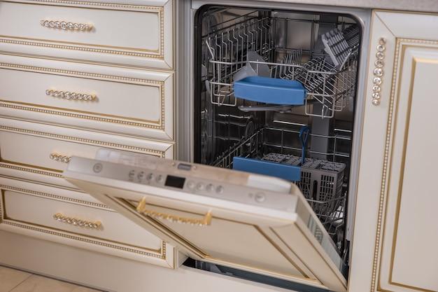 랙과 몇 가지 요리를 공개하는 열린 도어와 식기 세척기 기기의 주방 세부 사항