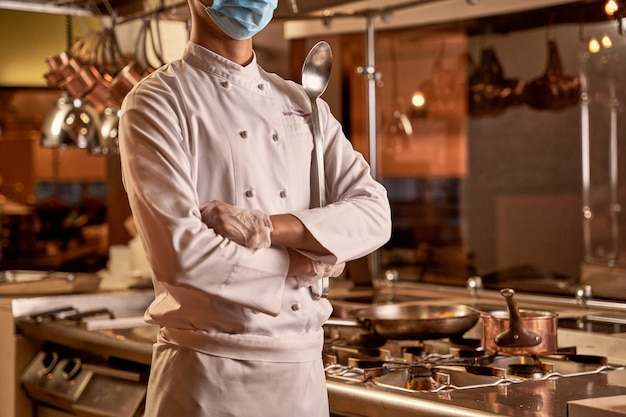 鍋とフライパンで炊飯器の横にいる間、胸の下で手を交差させるキッチンの従業員
