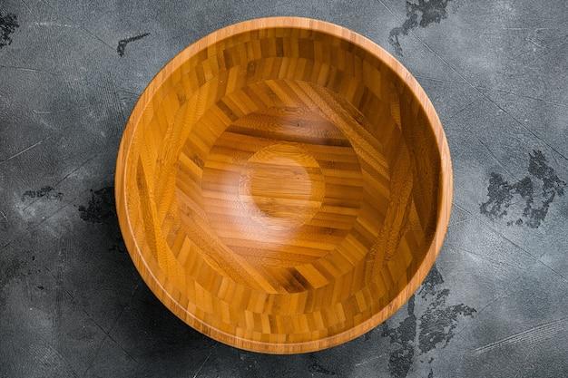 텍스트나 음식을 위한 복사 공간이 있는 샐러드용 주방 빈 나무 그릇, 회색 석재 테이블 배경 위에 있는 평면도