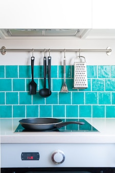 Kitchen features dark gray flat front cabinets paired with white quartz countertops and a glossy blue care tile.