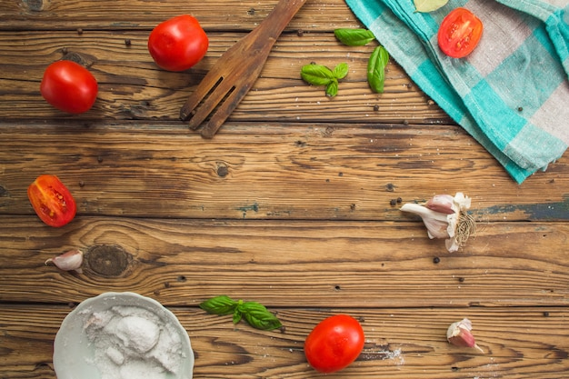 Kitchen flat lay on wooden background with tomatoes, basil, garlic, turquoise tablecloth. blank copy space in the center. top view banner