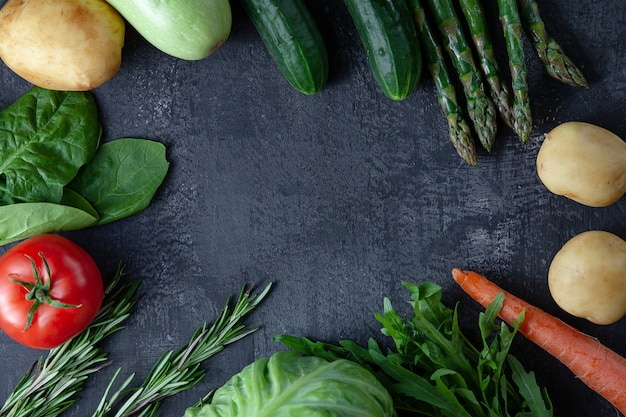Kitchen - fresh colorful organic, eco young spring vegetables on dark stone background. carrots, tomatoes, parsley, asparagus and rosemary flat lay. top view vegan food. ingridients with copy space