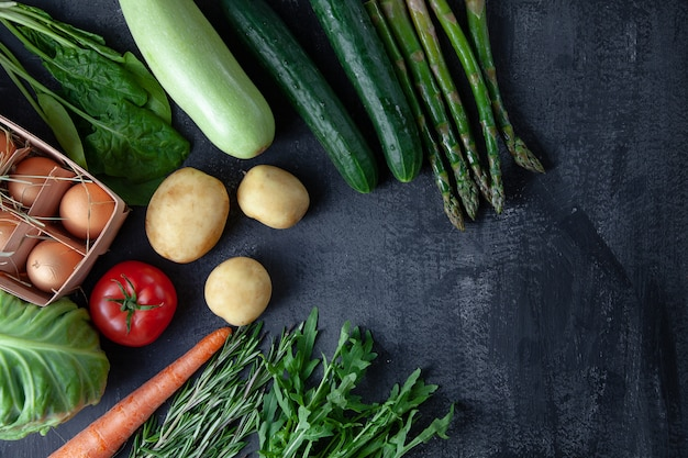 Kitchen - fresh colorful organic, spring vegetables on dark stone background. carrot, tomato, parsley, asparagus and rosemary flat lay. top view vegan food. ingridients with copy space. green cocnept