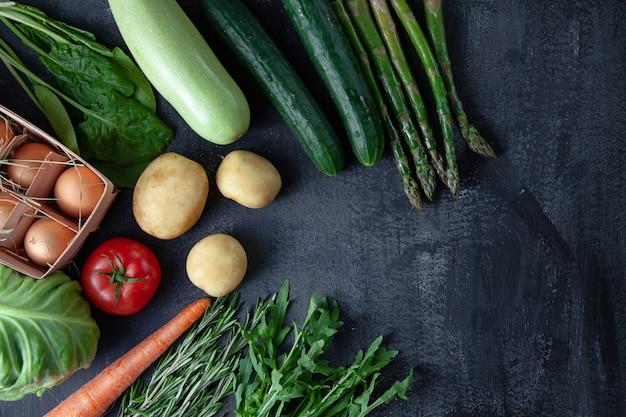 부엌-어두운 돌 배경에 신선한 다채로운 유기, 봄 야채. 당근, 토마토, 파슬리, 아스파라거스 및 로즈마리 평면 배치. 상위 뷰 채식 음식. 복사 공간이있는 ingridients 녹색 cocnept