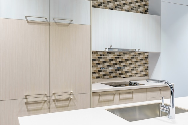 Kitchen furniture with contemporary kitchenware like hood, faucet and sink in house.