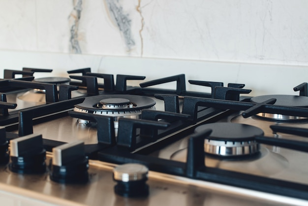 キッチンガスストーブ、クローズアップ。モダンなキッチンの新しいガスストーブ器具とカウンタートップの表面。モダンなキッチンストーブクック。