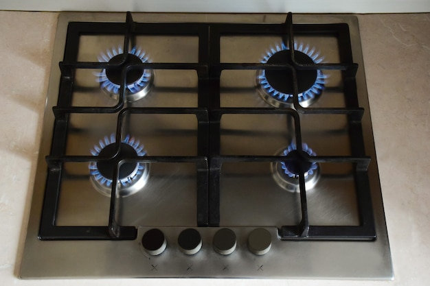Kitchen gas stove with four red-hot burners burning blue flame