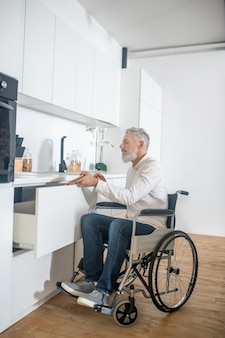 In the kitchen. gray-haired handicapped man in the kitchen getting the breakfast ready