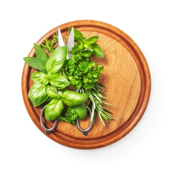 Kitchen herbs on cutting board fresh basil parsley peppermint rosemary and scissor