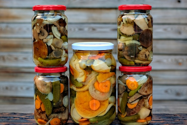 Kitchen and homemade concept: forest mushrooms in jars on a wooden background.