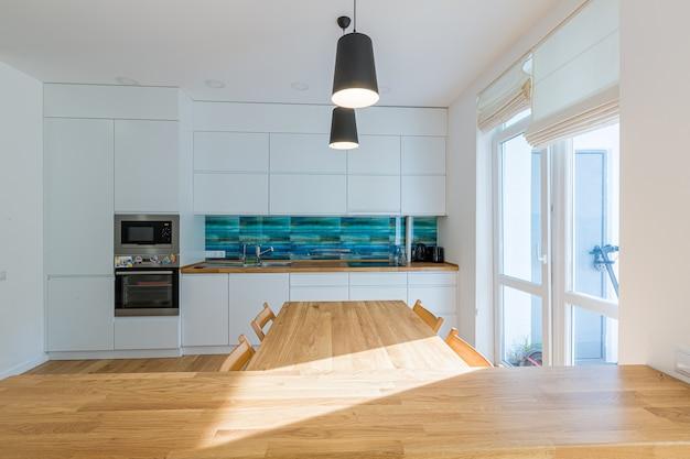 밝은 색상의 큰 테이블이있는 현대적인 스타일의 주방