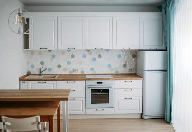 Интерьер кухни в белых тонах с деревянными столешницами и голубыми мятными шторами, классический стиль. идея дизайна для маленькой семьи