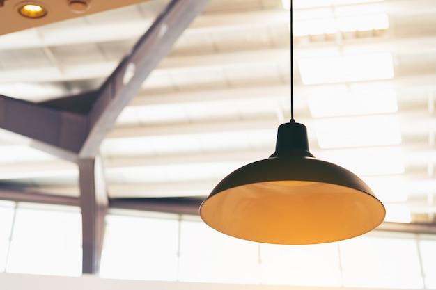キッチンインテリアまたは金色の光の大きな黒いランプ付きのレストラン。ロフトスタイル