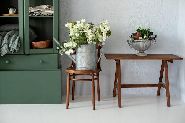 Интерьер кухни с деревенским декором и белыми цветами в серебряной лейке на деревянном стуле