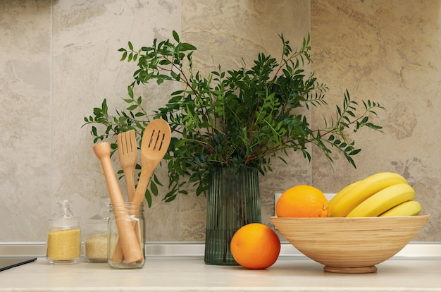Kitchen interior with supplies, fruits and plant
