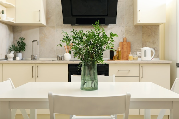 Kitchen interior with wooden table with vase with plant
