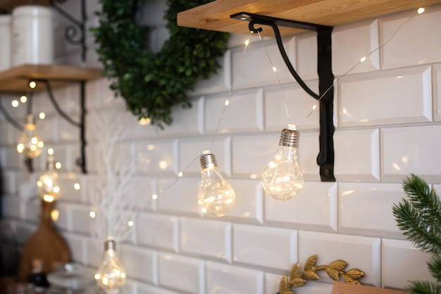 The kitchen is decorated with a garland of incandescent lamps. brick wall and shelves in light colors. cute and cozy. holiday, christmas