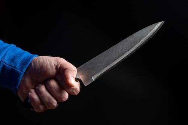 Кухонный нож в мужской руке крупным планом на черном