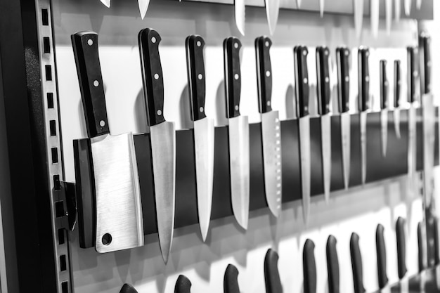 Kitchen knives collection on magnetic holder closeup. cooking equipment