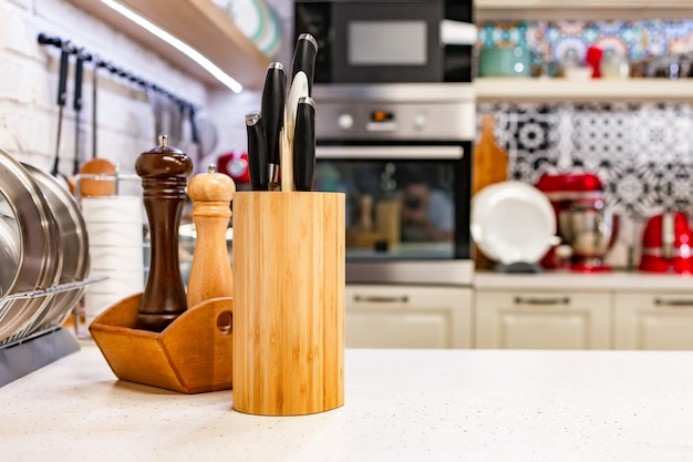 Kitchen knives in a special wooden stand with spice jars