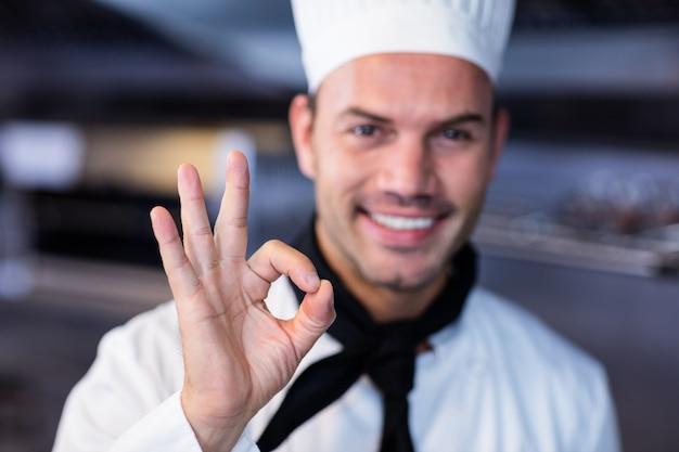 業務用kitchen房でokサインを作る幸せなシェフ