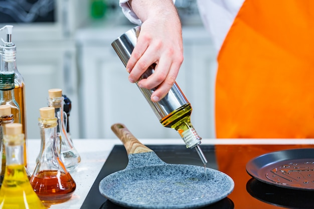 Kitchen preparation: the chef pour oil in a frying pan