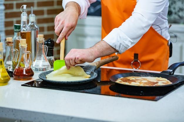 キッチンの準備:シェフが2つのフライパンで新鮮なパンケーキをフライします