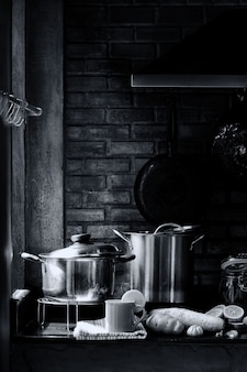 Kitchen room with kitchenware, stove, hood, and brick wall with a cup of lemon tea with vapor and steam. concept of chef or cook lover life. retro black and white image.