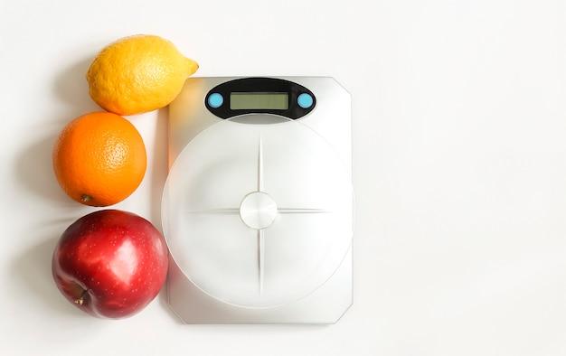 Кухонные весы на светлом фоне, рядом с фруктами, яблоком, апельсином и лимоном.