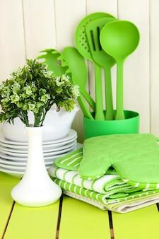 Кухонные принадлежности: посуда, прихватки, полотенца и прочее на деревянном столе.
