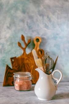 様々なハーブ、スパイス、種子、豆類、まな板、白の調理器具が付いている台所の棚