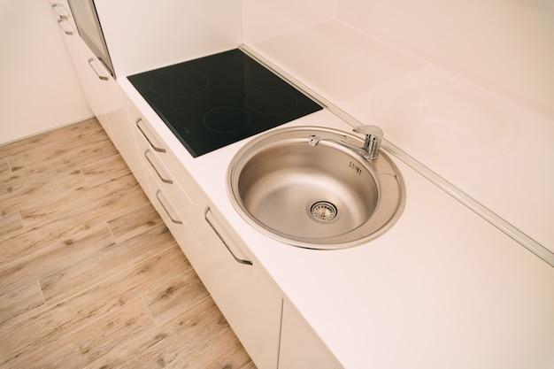 Кухонная раковина и повар с белыми шкафами