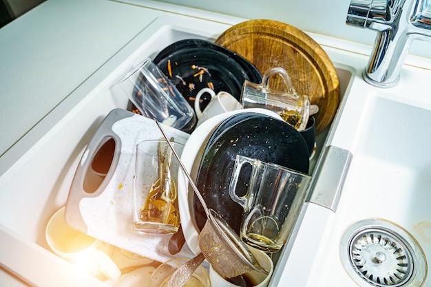 Кухонная раковина с грязной посудой и посудой. беспорядок и тонуть. грязная посуда.