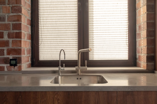 Kitchen sink with few faucets next to window and brick wall