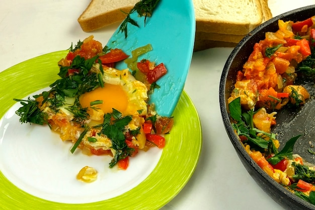 Kitchen spatula adds fried eggs shakshuka in vegetables sauce to plate. jewish and arabic cuisine.
