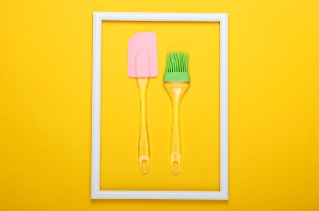 キッチンへらと白いフレームで黄色の表面にブラシ