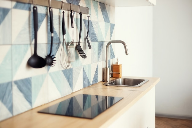 Kitchen spatulas handing on railing on a tiled wall with geometric pattern in modern kitchen room